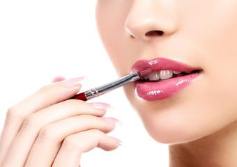 beautiful young woman applying lips makeup with cosmetic brush