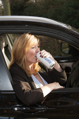 Woman driver drinking from a beer can