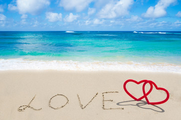 "Sign ""LOVE"" with hearts on the beach"