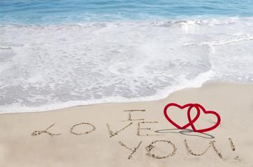 "Sign ""I love you"" on the sandy beach"