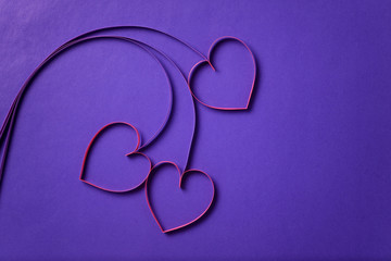 paper flowers with hearts on purple background