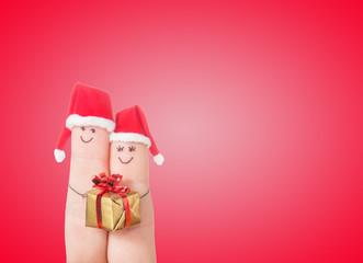 Fingers faces in Santa hats with gift box. Happy couple concept