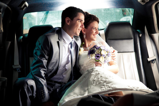couple sitting on backseat of the car and looking out of window