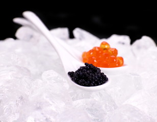 Porcelain spoon full of red and sturgeon black caviar