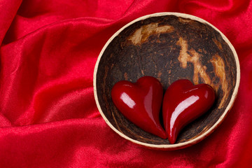 two hearts in a bowl of coconut on red satin background