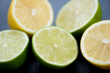 Ripe sliced limes and lemons, close-up, studio shot