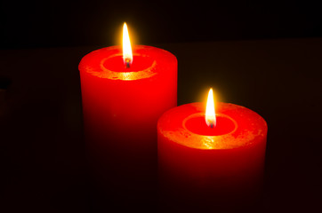 Close up of two red candles on black background