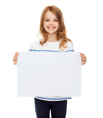 smiling little child holding blank white paper