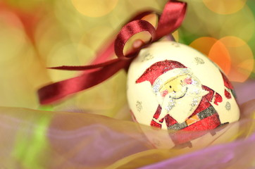 bożonarodzeniowe cacko zrobione techniką decoupage na tle bokeh