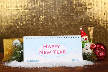 Calendar, New Year decor and fir tree on shiny golden