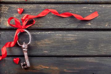 Schlüssel mit roter Schleife auf Holzbrett