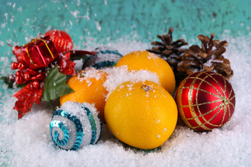 Christmas tangerines and Christmas toys on wooden table on snow