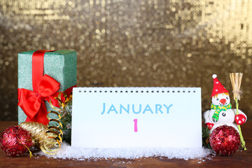 Calendar, New Year decor and fir tree on shiny golden