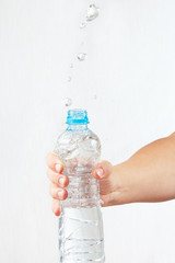 Female hand shaking small bottle of mineral water with splash