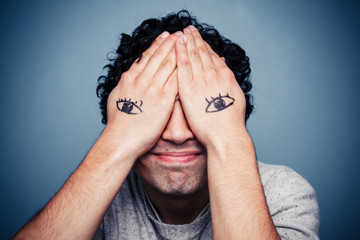 Man with eyes painted on his hands