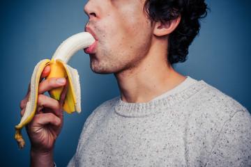 Young man eating banana
