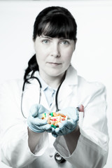 Doctor or pharmacist holding a pills in the hand