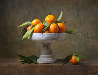 Vintage still life with tangerines in vase for fruits