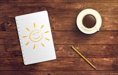 Notizblock mit Sonne Zeichnung Stift und Kaffee auf Holz Tisch