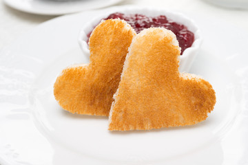 Two toast bread in the shape of hearts and berry jam, close-up