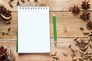 Notebook with green pencil and aromatic spices
