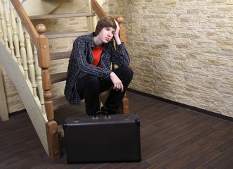 Teenage boy 14 years, sitting on wooden stairs near suitcase.