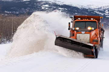 Snow plough clearing road in winter storm blizzard Wall mural