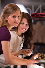 Two beautiful young girls choosing accessories at store