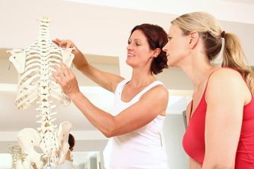 Physiotherapeutin erklaert Patientin die Schulter