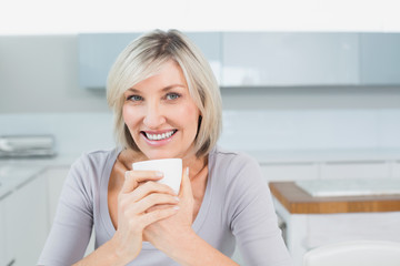 Smiling young woman with coffee cup in kitchen at home