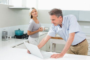 Man using laptop while woman in the kitchen