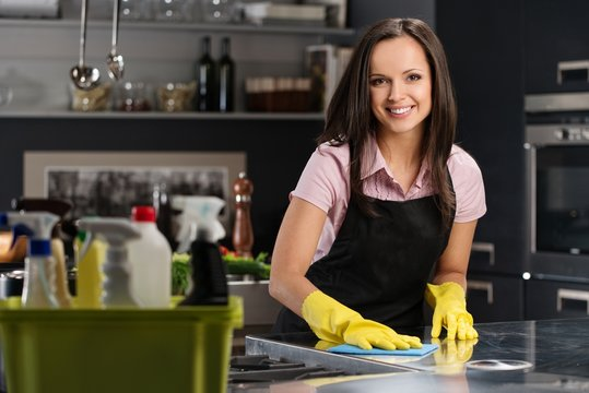 Beautiful woman in gloves cleaning modern kitchen