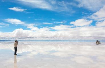 Man taking pictures on the lake Salar de Uyuni