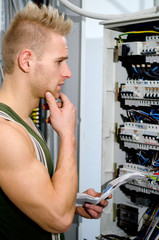 Confused male electrician in front of power panel