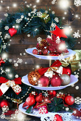 Christmas decorations on dessert stand, on wooden background