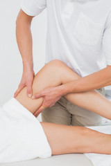 Male physiotherapist examining a woman's leg