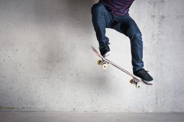 Skateboarder doing a skateboard trick - ollie - against concrete