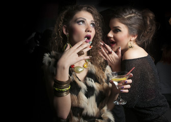 Two women  with martini drinks gossiping