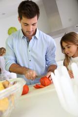 Man in kitchen preparing lunch with daughter