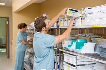 Nurses Arranging Stock In Storage Room Wall mural