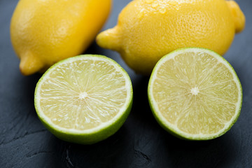 Sliced lime and whole lemons, black wooden background