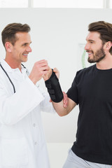 Male physiotherapist examining a young man's wrist