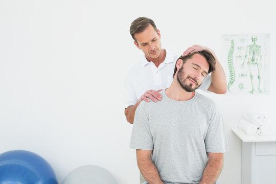 Male chiropractor doing neck adjustment