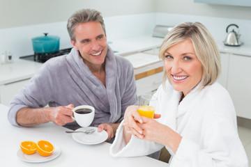 Happy couple in bathrobes having breakfast in kitchen