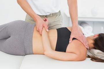 Male physiotherapist massaging woman's body
