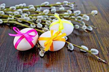 Easter eggs with ribbons and willow on the board