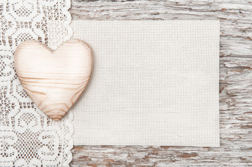 Wooden heart, lacy cloth and canvas on old wood