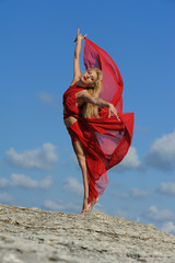 Woman in red dancing with clouds on air