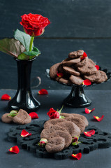 Chocolate chip cookies on a dark wooden table and a red rose