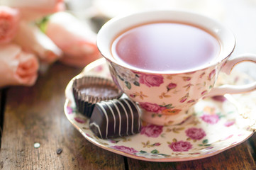 Close up of a cup of tea with roses and chocolate candies on woo